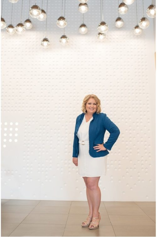 portrait of businesswoman standing in front of detailed wall